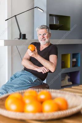 Man eating an orange