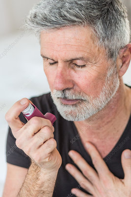Man using an inhaler during an asthma attack