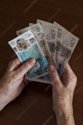 Elderly woman holding British banknotes