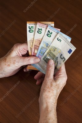 Elderly woman holding Euro banknotes