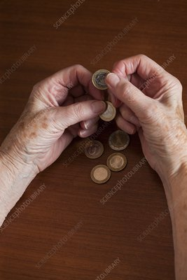 Elderly woman counting Euro coins in her hands