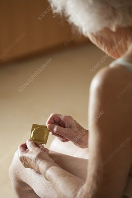 Close-up of elderly woman holding condom