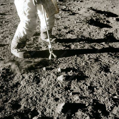 Apollo 12 astronaut using lunar hand tool, 1969