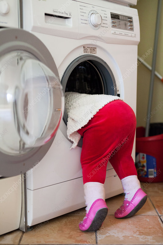 Baby girl with head inside washing machine