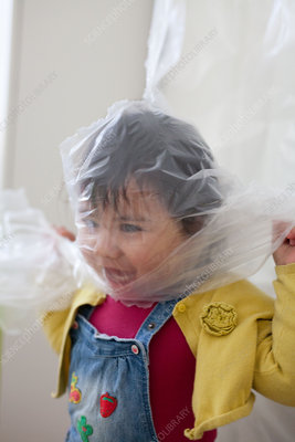 Baby girl with plastic bag around her head