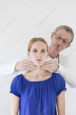 Doctor examining a patient's thyroid