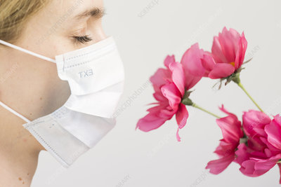 Woman wearing mask in front of flowers