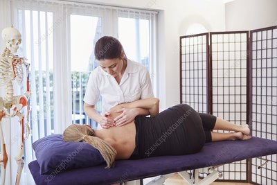Pregnant woman being treated by an osteopath