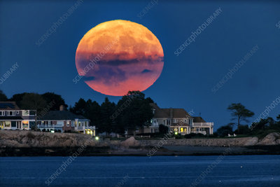 Full moon rising over oceanfront houses