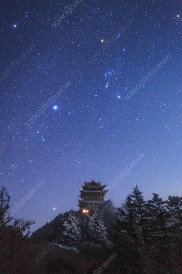 Orion in night sky above Buddhist temple