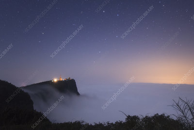 Night sky above clouds and Buddhist mountain