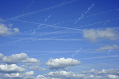 Vapour trails from aircrafts among clouds in a blue sky