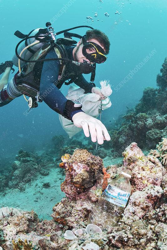 Scuba diver collecting waste plastic bottle