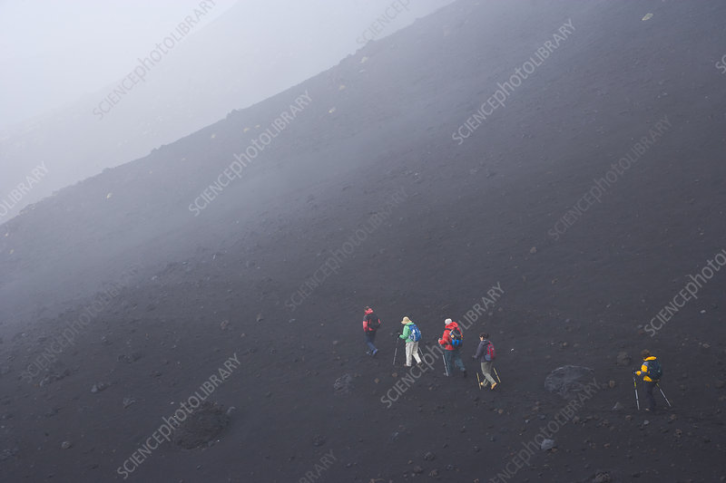 Hikers climbing Mount Etna in the mist, Sicily, Italy