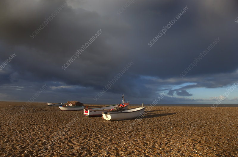 Boats on Cley Beach with stormy clouds above, UK