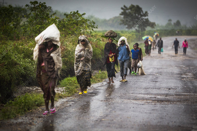 Villagers walking along a road during a heavy rain shower