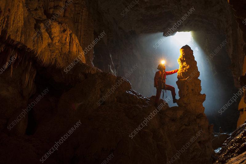 Potholer touching a stalagmite