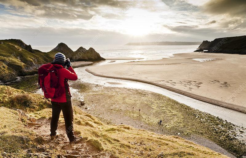 Man taking a photograph of Three Cliffs Bay, Wales, UK