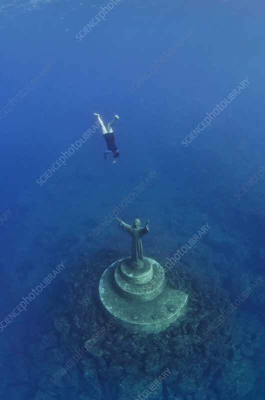 Fisherman diving to the statue of Christ Of The Abyss, Italy