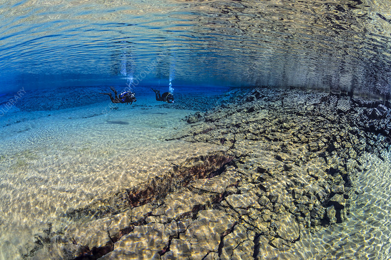 Pair of divers swimming in the blue lagoon, Silfraa, Iceland