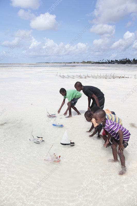 Racing toy boats on a beach, Zanzibar