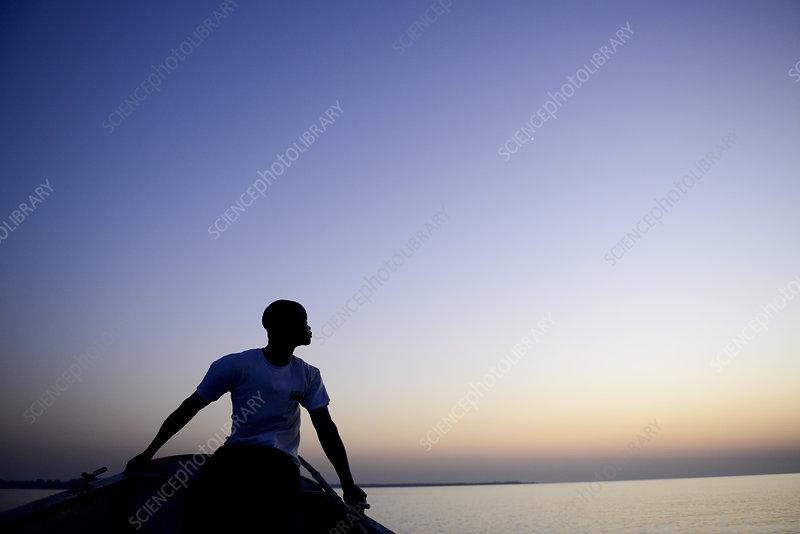 Man in open rowboat at dusk, Orango Island, Guinea-Bissau