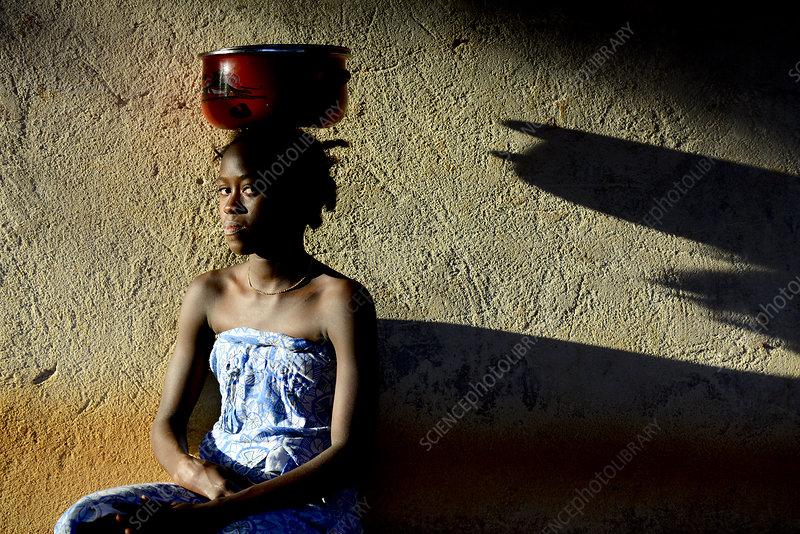 Nalu girl with metal bowl on head, Guinea-Bissau