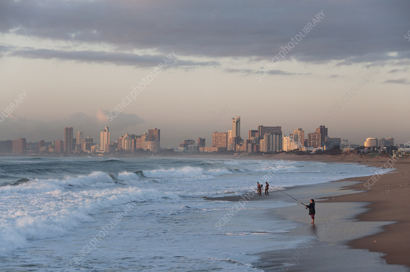 People on Durban beach at dawn with city in the distance