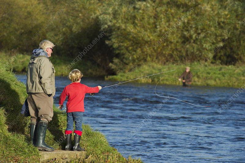 Family fishing from bank of the River Tweed, Scotland, UK