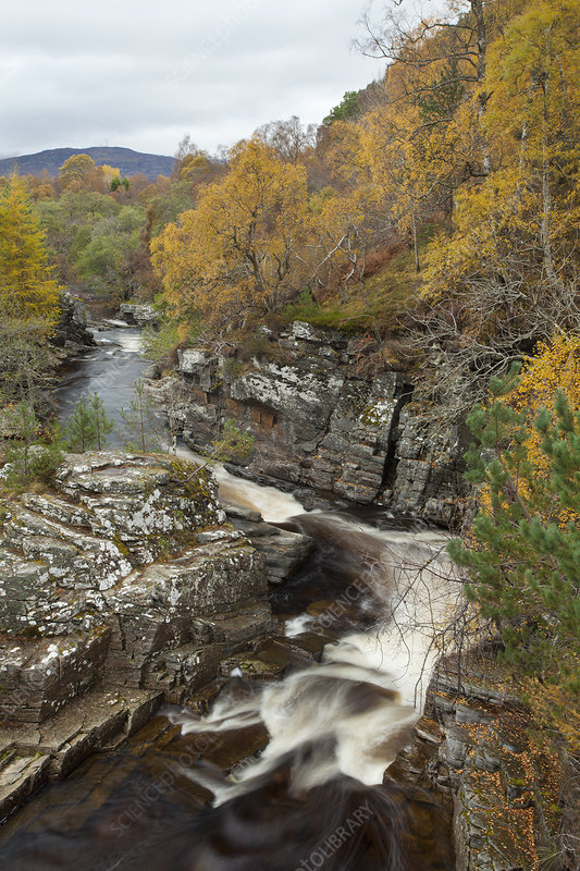 River flowing through gorge in autumn woodland