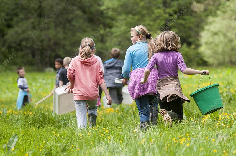 School children carrying equipment to release salmon fry