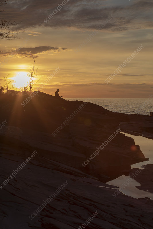 Man reading a book by a lake at sunset