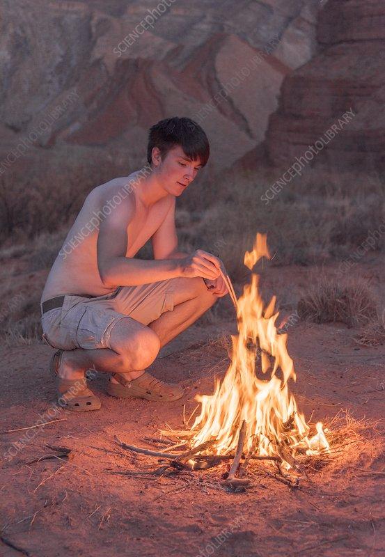 Young man lighting a campfire