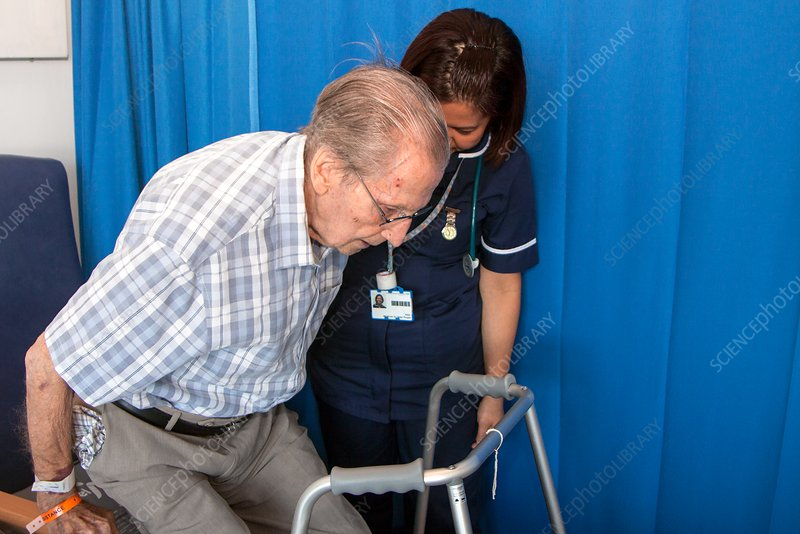 Elderly patient being helped by hospital nurse