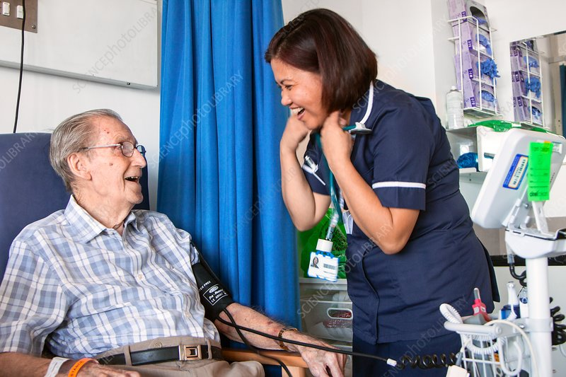 Elderly patient laughing with hospital nurse