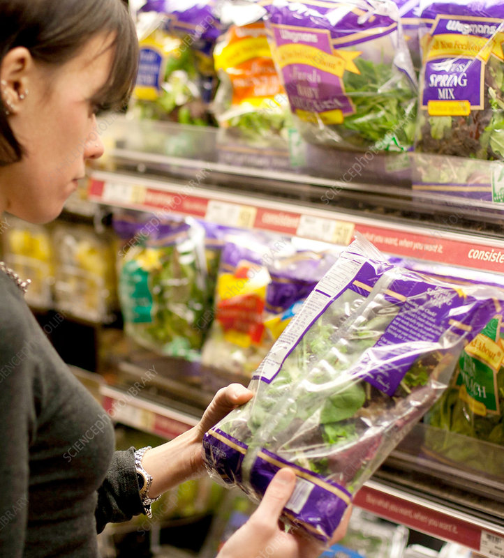 Woman Reading Nutrition Label of Greens