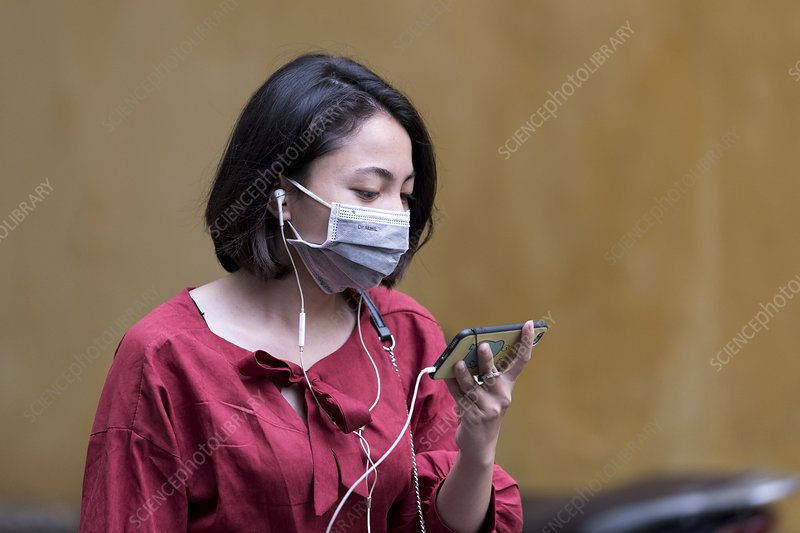 Woman with cell phone and face mask