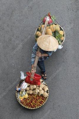 Vendor using a carrying pole in Hanoi, Vietnam