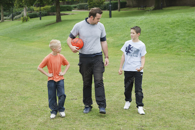 Man and boys walking along with football