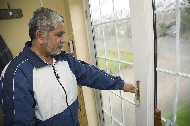 Older man checking that the front door is locked