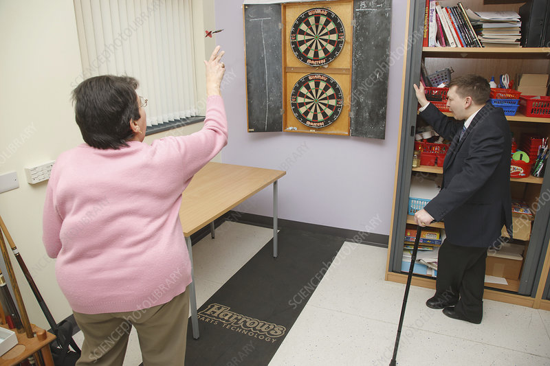Woman with scoliosis playing darts