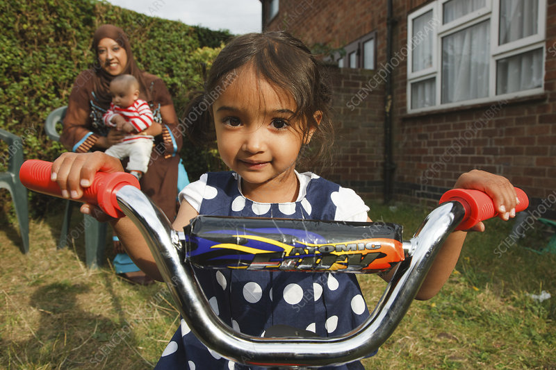 Girl on trike with mother behind