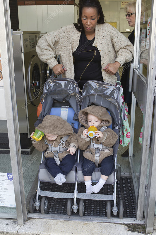 Mother with twins in buggy at launderette