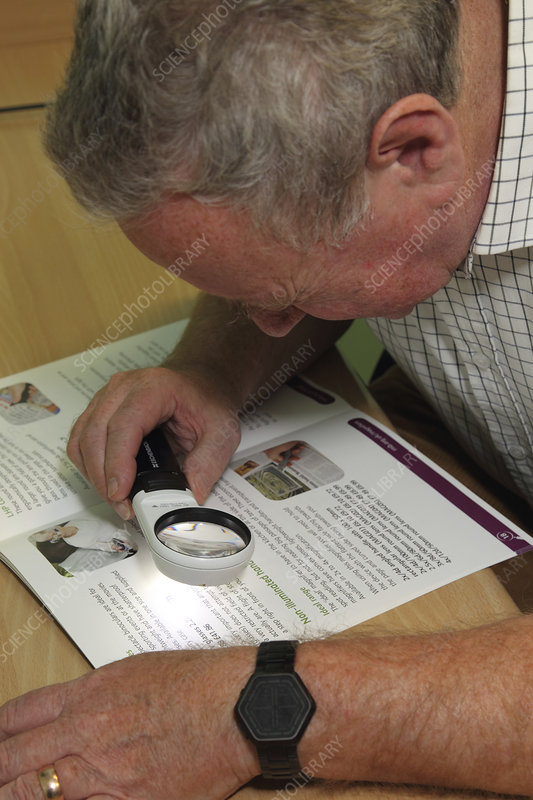 Using illuminated magnifier to look at brochure