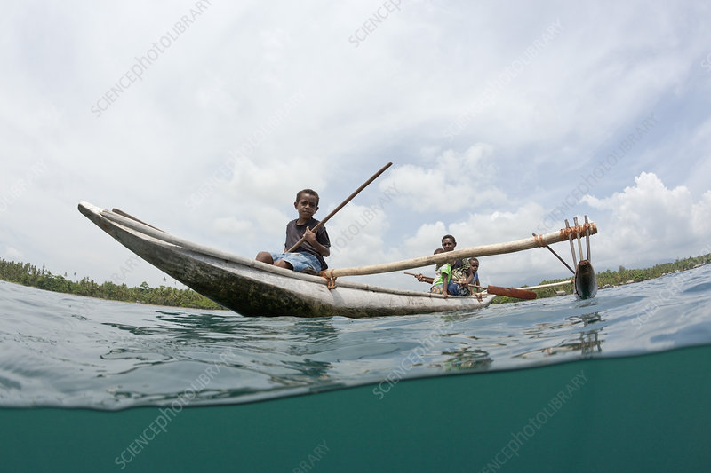 Family in outrigger canoe, Tufi, Papua New Guinea