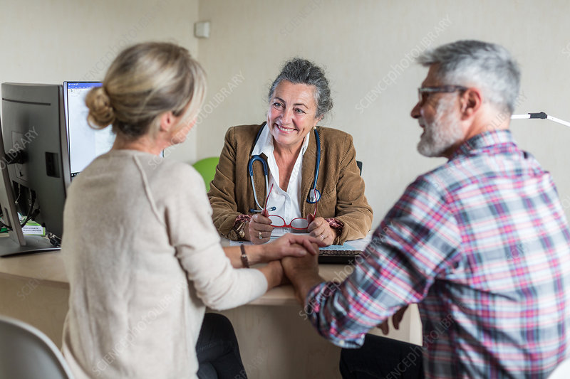 Doctor discussing with a couple during consultation