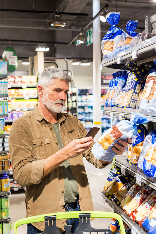 Man using an app on his smartphone in a supermarket