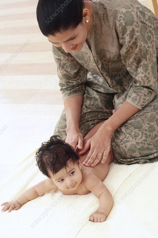 Woman massaging baby