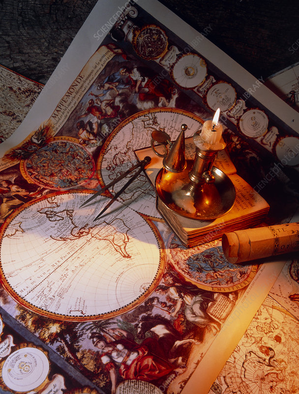 Lighted candle on top of historical maps