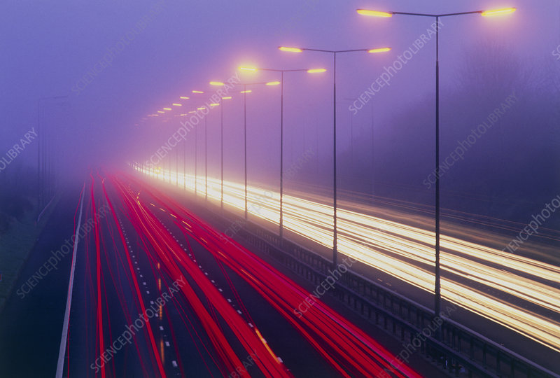 Time exposure image of car lights on a foggy road